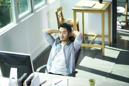 Foto de young asian business man looking at computer monitor with satisfaction, hands behind head. - Imagen libre de derechos