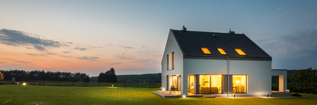 Foto de Panoramic photo of modern house with outdoor and indoor lighting, at night - Imagen libre de derechos