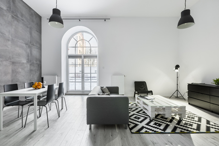 Foto de Modern loft interior with sofa, dining table with chairs, studio lamp and big window - Imagen libre de derechos