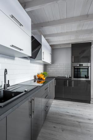 Foto de Modern, black and white kitchen with wooden ceiling - Imagen libre de derechos