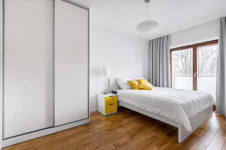 Photo for Modern bedroom with white wardrobe and double bed - Royalty Free Image