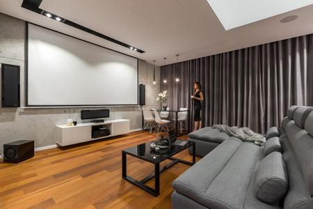 Foto de Woman in living room with projector screen, gray sofa and black coffee table - Imagen libre de derechos