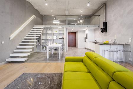 Foto de Storied loft apartment with green couch, carpet and transparent coffee table - Imagen libre de derechos