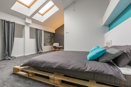 Photo for Simple attic bedroom with diy pallet bed and windows in ceiling - Royalty Free Image