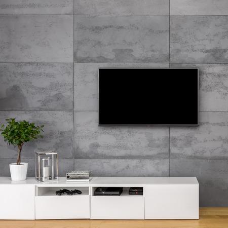 Photo pour Apartment with tv, white cabinet and concrete wall - image libre de droit
