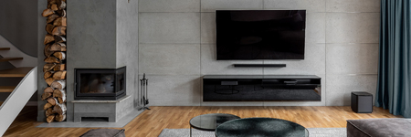 Foto de Tv living room with cement wall and wall mounted fireplace, panorama - Imagen libre de derechos