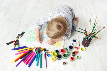 Photo pour Child drawing picture with crayon  in album using a lot of painting tools. Top view. Creativity concept. - image libre de droit