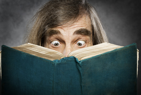 Photo pour Senior reading open book, surprised old man, amazing eyes looking blank cover - image libre de droit