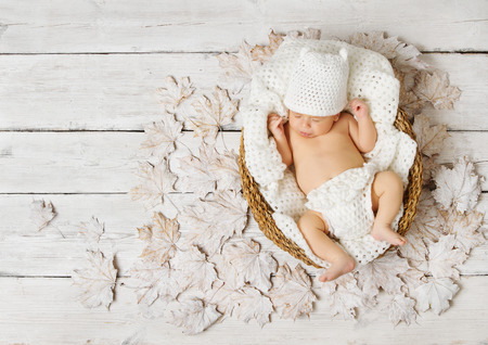 Photo for Newborn baby sleeping in basket on leaves over white wooden background. - Royalty Free Image