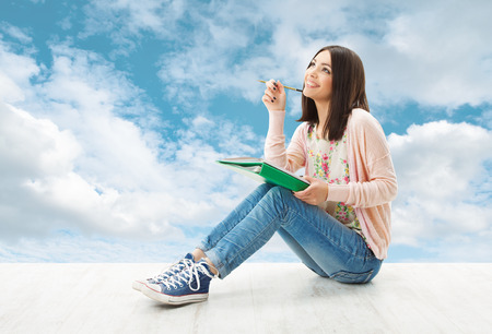 Photo for Girl teenager thinking inspiration or write idea, sitting over blue sky background  - Royalty Free Image
