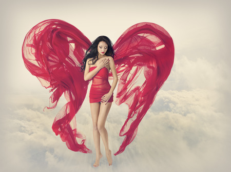 Woman Angel Wings as Heart Shape of Fabric Cloth, Fashion Model Girl in Red Dress, Flying on Fantasy Sky Clouds Background