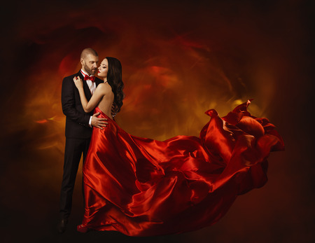 Foto de Elegant Couple Dancing in Love, Woman in Red Clothes and Lover Man in Classic Suit, Long Waving Dress Tail, Fashion Beauty Portrait - Imagen libre de derechos