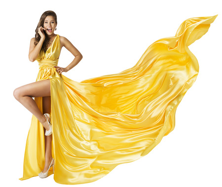 Photo pour Woman Beauty Fashion Dress, Beautiful Girl In Flying Yellow Fluttering Gown, Standing on One Leg High Heels, Surprised with Open Mouth. Fabric Cloth Waving on Wind, Isolated Over White Background - image libre de droit