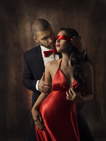Foto de Couple in Love, Sexy Fashion Woman and Man, Girl with Red Band on Eyes Charming Boyfriend in Suit, Glamor Model Portrait, Valentine Day Lovers Sensual Games - Imagen libre de derechos