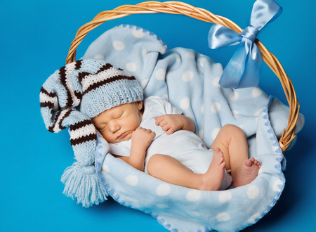Photo pour Newborn Baby Inside Basket, New Born Kid Dream in Woolen Hat, Little Child Boy Sleeping over Blue Background - image libre de droit