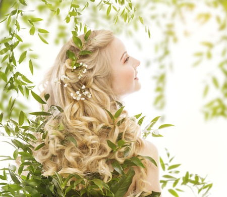 Photo pour Hair in Green Leaves, Natural Treatment Care, Woman with Long Curly Blond Hairs, Back view over White - image libre de droit