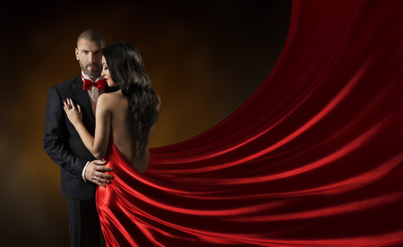 Foto de Couple Beauty Portrait, Man in Suit Woman in Red Dress, Rich Lady in Gown, Waving Silk Fabric - Imagen libre de derechos