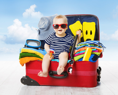 Foto de Baby in Travel Suitcase. Kid inside Luggage Packed for Vacation Full of Clothes, Child and Family Trip - Imagen libre de derechos