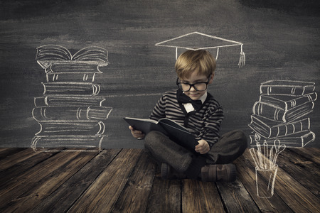 Foto de Child Little Boy in Glasses Reading Book over School Black Board with Chalk Drawing, Kids Preschool Development, Children Education Concept - Imagen libre de derechos