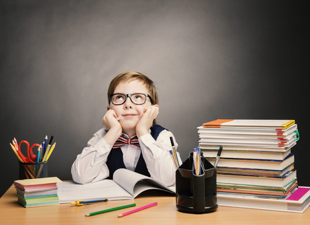 Foto de School Child Boy in Glasses Think in Classroom, Kid Primary Students Reading Book, Excellent Pupil Learn Lesson and Dream, Education Concept - Imagen libre de derechos