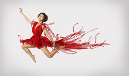 Woman Running in Jump Girl Performer Leap Dancing in Red Dress over light gray background