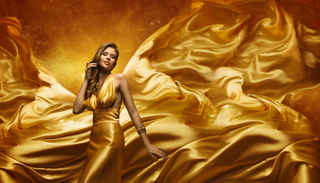 Photo pour Fashion Model in Gold Dress, Beauty Woman Posing over Flying Waving Cloth, Girl with Yellow Dynamic Silk Fabric - image libre de droit