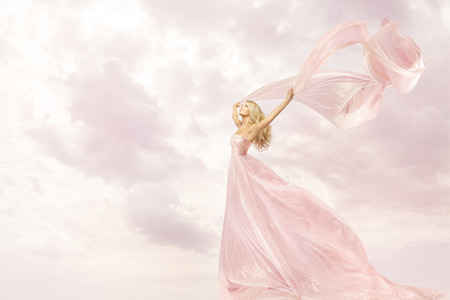 Photo for Happy Woman in Pink Long Dress, Girl with Flying Silk Scarf Cloth, Joy Open Arms Freedom concept - Royalty Free Image