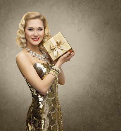 Foto de Rich Woman with Gift Box, Luxury Retro Girl in Shining Gold Dress, Yellow Golden Present for VIP Lady - Imagen libre de derechos