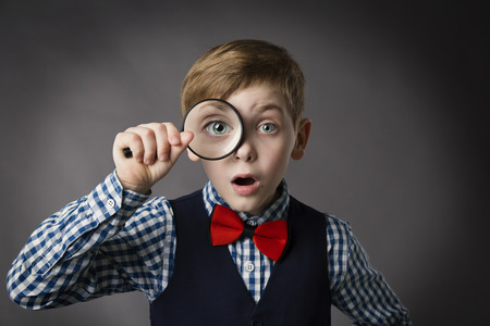 Foto de Child See Through Magnifying Glass, Kid Eye Looking with Magnifier Lens, Gray Background - Imagen libre de derechos