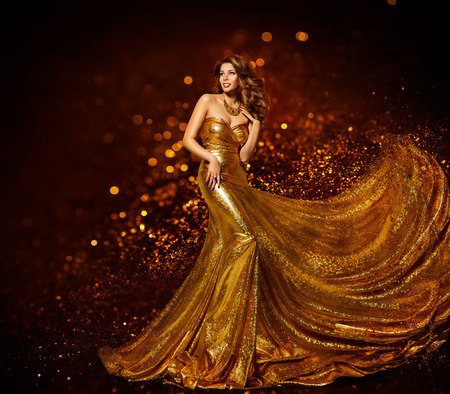 Foto de Fashion Woman Gold Dress, Luxury Girl in Elegant Golden Fabric Gown, Flying Sparkles Cloth - Imagen libre de derechos