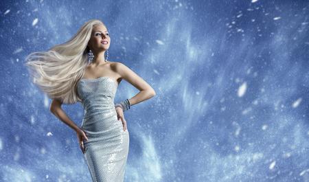 Photo pour Woman Elegant Fashion Dress, Long Hair Waving on Wind, Beauty Model Posing over Blue Winter Background - image libre de droit