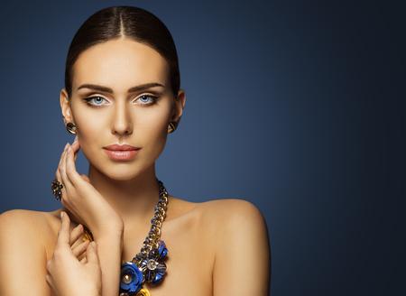 Photo pour Woman Beauty Face Makeup, Beautiful Fashion Model Make Up Portrait, Elegant Lady Touching Face Skin, Blue Jewelry - image libre de droit
