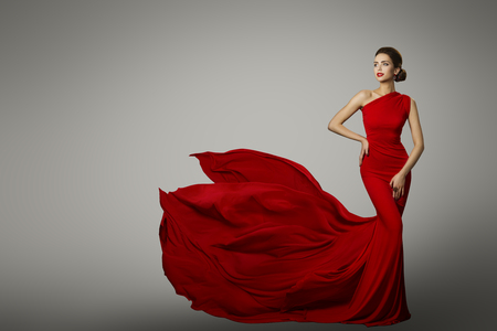 Foto de Fashion Model in Red Beauty Dress, Sexy Woman posing evening Gown, Flying Silk Tail over gray background - Imagen libre de derechos