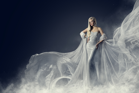 Foto de Fashion Model Beauty Dress, Waving Silver Cloth Gown, Woman in White Fluttering Clothes Fabric, over Night Background - Imagen libre de derechos