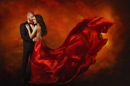 Photo for Elegant Couple, Dancing Woman in Red Dress Fluttering Flying on wind and Man in Black Suit, Love Beauty Portrait - Royalty Free Image