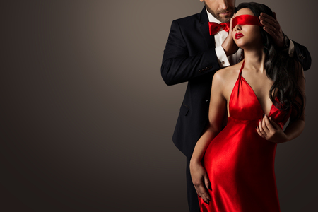 Photo pour Couple Love Kiss, Sexy Blindfolded Woman Dancing in Red Dress and Elegant Man in Suit - image libre de droit