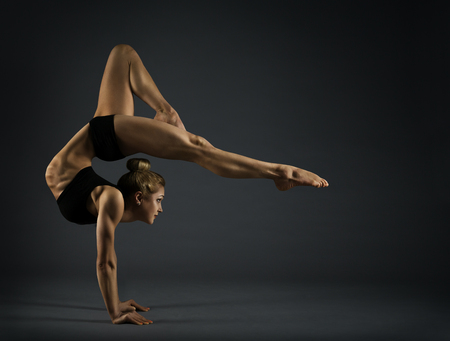 Photo pour Flexible Woman Circus Gymnast, Gymnastics Hand Stand, Young Acrobat Standing on Hands, Yoga Headstand Backbend Exercise over black background - image libre de droit