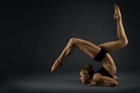Photo for Yoga Gymnastics Pose, Woman Flexible Body, Gymnast Balance in Backbend Exercise, Acrobat Back Bend Position, Girl Posing on Black Background - Royalty Free Image