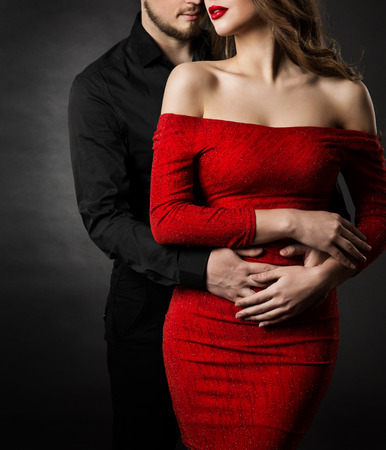 Foto de Couple Fashion Beauty, Young Woman in Sexy Red Dress and Embracing Man in Love - Imagen libre de derechos