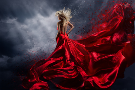 Foto de Woman in Red Dress Dance over Storm Sky, Gown Fluttering Fabric Flying as Splash - Imagen libre de derechos