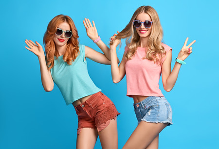 Photo for Fashion Hipster woman Having Fun Crazy Cheeky Dance. Hipster Sisters Best Friends Twins in Stylish Summer Outfit. Funny Model Girl Fashion Sunglasses.Glamour fashion Trendy Hairstyle, dancing.Creative - Royalty Free Image