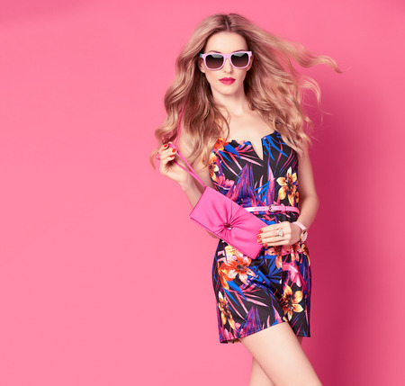 Photo pour Fashion woman in Trendy Spring Summer Dress. Stylish wavy hairstyle, fashion Sunglasses, Summer Floral Outfit. Glamour Blond lady in Sexy Jumpsuit, fashion pose. Playful Girl,Luxury summer Pink Clutch - image libre de droit