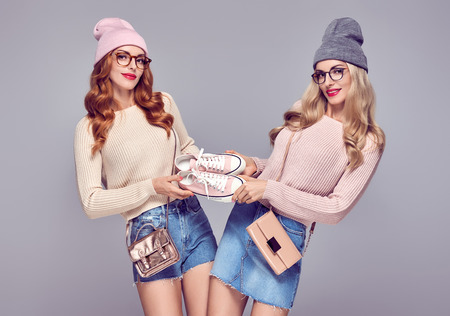 Photo for Young Woman Having Fun Crazy. Fashion. Shopping Sales Discount concept. Pretty Sisters Best Friends Twins in Stylish fashion Autumn Winter Outfit. Playful Hipster Model Girl in Cozy Jumper, Glasses - Royalty Free Image