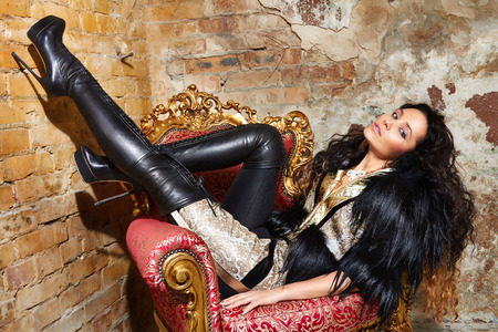 Foto de Beautiful sexy woman long brunette hair in black fur Treads on high heel gold pans sitting on the chair red brick wall background makeup fashion style - Imagen libre de derechos