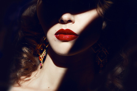 Photo for Closeup of the face belong to beautiful young sexy blonde girl with curly hair pure snow white skin and bright makeup red lips, red lipstick, long earrings in dark shadows of palm leaves - Royalty Free Image