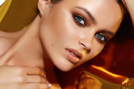 Foto de Beautiful sexy young woman evening make up dark eye eyelashes dyed brunette waves stacked hair nude shoulder Golden Tan looks into the camera makeup artist cosmetic beauty salon spa - Imagen libre de derechos