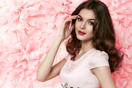 Photo pour Beautiful young sexy girl with long wavy brunette hair with a bright evening make-up perfect summer tan thin figure dressed in colored short dress holding flower pink - image libre de droit
