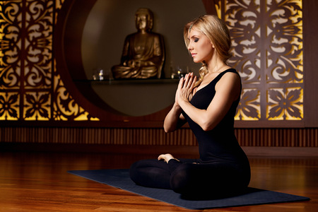 Foto de Beautiful young sexy blond girl with a sporty physique slender figure doing yoga exercises  fitness in suit meditates relaxes pilates - Imagen libre de derechos