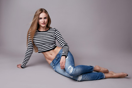 Photo for Beautiful young sexy woman with long blonde hair with natural make-up wearing jeans and pirates top sitting on the floor model with a clothing catalog spring collection style and fashion - Royalty Free Image