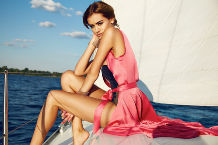 Foto de Beautiful young sexy brunette girl in a dress and makeup, summer trip on a yacht with white sails on the sea or ocean in the Gulf marine of the wind and the breeze in the sun tans romantic - Imagen libre de derechos